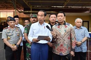 Indonesia's President Joko Widodo (centre) and other officials holding a press conference in Surabaya after a series of suicide bombings, on May 13, 2018.