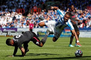 Arsenal's Alexandre Lacazette in action with Huddersfield Town's Mathias Jorgensen at the John Smith's Stadium, Huddersfield, Britain on May 13, 2018.
