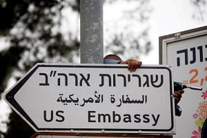 A worker hangs a road sign directing to the US embassy in Jerusalem on May 7, 2018.
