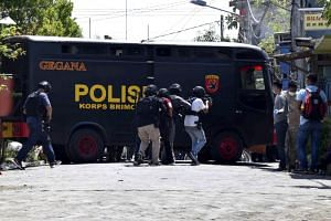 Indonesian anti-terror police officers approach the house of a family said to have carried out bombing attacks, during an anti-terror raid in Surabaya, on May 15, 2018.
