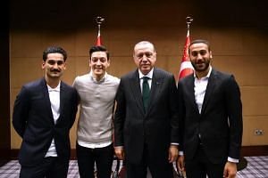 Turkish President Recep Tayyip Erdogan(second right) poses for a photo with Turkish football players Ilkay Gundogan (left), Mesut Ozil (second left) and Cenk Tosun (right) in London, on May 13, 2018.