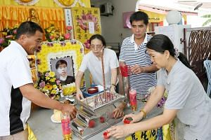 (From left) Corporal Kok Yuen Chin's uncle Kok Min Kweh, aunt Helen Kok, father Kok Meng Hwa and mother Wong Siew Fong at his wake in his parents' home in Melaka yesterday. The 22-year-old, who died on Sunday during celebrations for his ORD, was foun