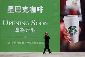 A man walks past an advertisement board of Starbucks in Wuhan, Hubei province, China, on Oct 29, 2013.