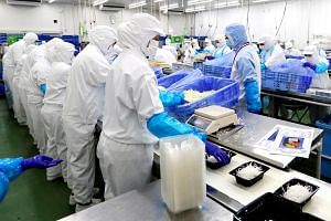 Workers packing salads at Delicious Cook & Co's food factory in Narashino, Japan, on April 17, 2018.