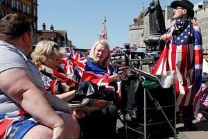 Tourists hold Union flags whilst draped in Union and US flags near Windsor Castle in Windsor, west of London on May 15, 2018.