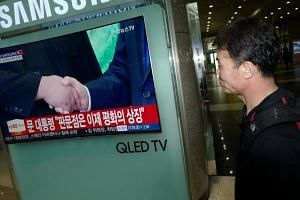 A public screen shows news coverage of South Korea's President Moon Jae In and North Korean leader Kim Jong Un shaking hands during their inter-Korean summit meeting, at a railway station in Seoul on April 27, 2018.