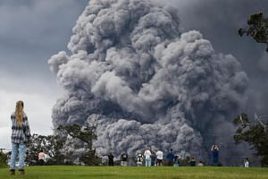 People watch at a golf course as an ash plume rises in the distance from the Kilauea volcano on May 15, 2018.