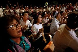 People hold a vigil for the victims of the suicide bomb attacks in Surabaya and Mobile Brigade headquarters in Depok near National monument in Jakarta, on May 15, 2018.