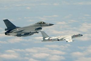 A Republic of China (Taiwan) Air Force F-16 fighter aircraft (left) flying alongside a Chinese People's Liberation Army Air Force H-6K bomber.