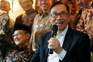 Malaysian politician Anwar Ibrahim speaking to the media during a visit to the home of former Indonesian president B.J. Habibie (left) in Jakarta on May 20, 2018.