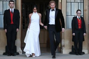The newly married Britain's Prince Harry, Duke of Sussex, (right) and Meghan Markle, Duchess of Sussex, leave Windsor Castle in Windsor on May 19, 2018 after their wedding to attend an evening reception at Frogmore House.