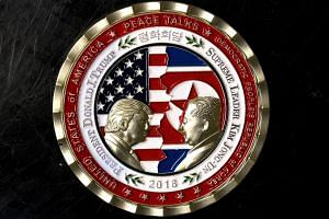 The coin depicts US President Trump and North Korean leader Kim Jong Un in profile facing each other in front of a background of US and North Korean flags.