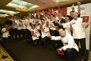Chefs and representatives of the restaurants that received a Michelin star during the launch of the second edition of the Michelin Guide Singapore at Fullerton Hotel on June 29, 2017.