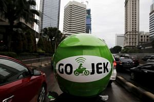 A Go-Jek motorist riding his motorcycle through Jakarta's business district.