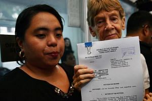 Australian nun Patricia Fox (right) shows documents of her deportation appeal she filed with her lawyer Catherine Panguban at the Department of Justice office in Manila, on May 25, 2018.