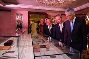 Prime Minister Lee Hsien Loong viewing the items of a time capsule that will be placed on June 1 in JTC's first permanent headquarters at Jurong Town Hall. With him are (from left) Datuk Seri Lim Chong Keat, architect of the original Jurong Town Hall