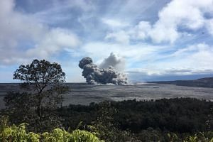 A general view taken from the caldera rim near Volcano House of rising ash plume from Halema'uma'u crater at the summit of the Kilauea Volcano, Hawaii, on May 24, 2018.
