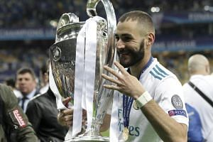 Real Madrid's French forward Karim Benzema (left) holds the trophy after winning the UEFA Champions League final football match between Liverpool and Real Madrid at the Olympic Stadium in Kiev, Ukraine, on May 26, 2018.