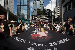 Protesters carry banners and chant slogans during a march to commemorate the 4 June 1989 Tiananmen Square massacre in Hong Kong, China, 27 May 2018.