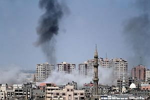 Smoke billowing in Gaza City on Tuesday, following an Israeli air strike on the Palestinian enclave. Militants from Hamas and Islamic Jihad fired dozens of rockets and mortar bombs at southern Israel throughout Tuesday and overnight, to which Israel