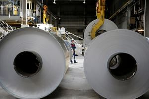 An operator uses a hoist to lift a coil of aluminium at the Neuf-Brisach Constellium aluminium products company's production unit in Biesheim, Eastern France, on April 9, 2018.