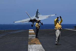 Sailors on flight deck duty as an FA-18 hornet fighter jet took off during routine training aboard US aircraft carrier Theodore Roosevelt in the South China Sea in April. As defence officials gather to discuss some of the Indo-Pacific's most pressing