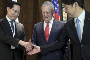 US Defence Secretary James Mattis looks on as South Korean National Defense Minister Song Young Moo (left) and Japanese Defense Minister Itsunori Onodera shake hands at a meeting on June 3, 2018.