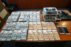 Police seized $590,000 in cash from the two men during a raid in Ubi Avenue 1 on June 4, 2018.