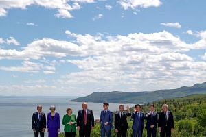 G7 leaders pose for a group photo at the G7 Summit in the Charlevoix city of La Malbaie, on June 8, 2018.
