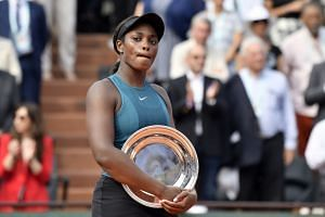 Stephens reacts with the runner-up trophy after losing to Simona Halep of Romania.