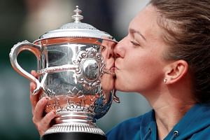 Romania's Simona Halep celebrates by kissing the trophy after winning the final against Sloane Stephens of the US.