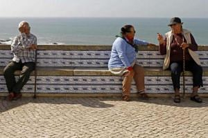 Senior citizens chat at a sea coast belvedere in Ericeira on the outskirts of Lisbon on Oct 29, 2011.