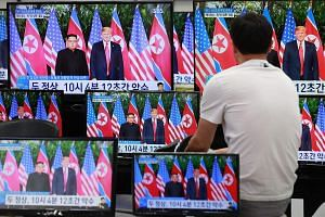 A man watches television screens showing the summit between US President Donald Trump and North Korean leader Kim Jong Un, at a shopping centre in Seoul, on June 12, 2018.