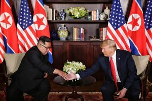 US President Donald Trump and North Korean leader Kim Jong Un shake hands at the historic summit in Singapore on June 12, 2018.