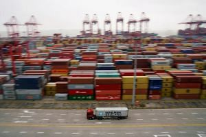 A container truck moves past containers at the Yangshan Deep Water Port in Shanghai, China, on April 24, 2018.