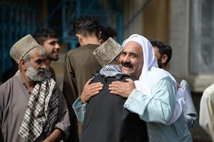 Afghan Muslims hug each other after offering prayers at the start of the Eid al-Fitr holiday, which marks the end of Ramadan, at the Shah-e Do Shamshira mosque in Kabul on June 15, 2018.