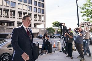 A protester holding up a sign as Paul Manafort, President Donald Trump's former campaign chairman, arrives at the federal courthouse in Washington for an arraignment hearing on Friday. The judge later ordered that he await trial in jail, a spectacula