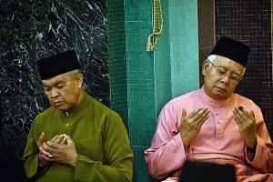 Former deputy prime minister Ahmad Zahid Hamidi and former prime minister Najib Razak performing evening prayers at Umno headquarters in Kuala Lumpur on May 11. Umno has no charismatic leader to replace Mr Najib, who resigned as party president after