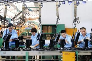 Employees working on a production line for domestic appliances at a factory in Jiujiang, Jiangxi province, on April 19, 2018.