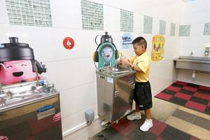 A Riverside Primary School pupil refilling his bottle at a water cooler. Health Minister Gan Kim Yong wants to saturate Singapore with readily available drinking water to wean people off sweetened drinks.