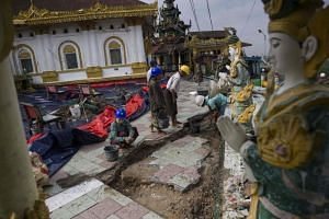 Workers repairing the grounds of the hilltop Kyeik Than Lan pagoda, which has been damaged by a landslide caused by flooding  in southern Myanmar, on June 18, 2018.