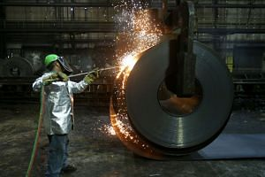 A worker cuts a piece from a steel coil at the Novolipetsk Steel PAO steel mill in Farrell, Pennsylvania.