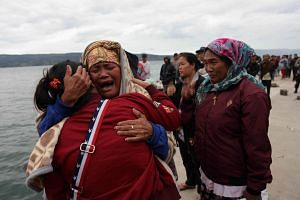 Relatives cry while waiting for news on missing family members who were on a ferry that sank in Lake Toba, North Sumatra, Indonesia, on June 19, 2018.
