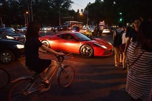 A driver in a Ferrari waits for pedestrians at an intersection in Beijing, China. Global wealth is on course to exceed US$100 trillion by 2025.