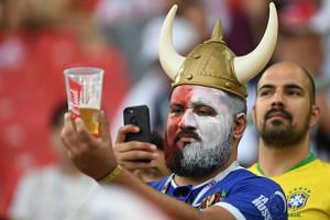 A fan sporting a viking helmet takes a photo of his beer before the Russia 2018 World Cup Group H football match between Poland and Senegal at the Spartak Stadium in Moscow on June 19, 2018.