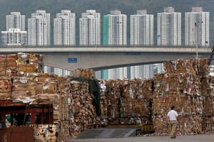 Tonnes of waste paper to be shipped to mainland China are piled up at a dock in Hong Kong.