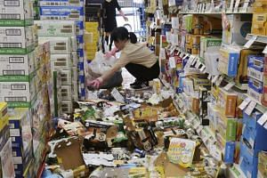 Employees picking up bottles and cans of beverages which were scattered by the earthquake at a liquor shop in Hirakata, Osaka, yesterday.