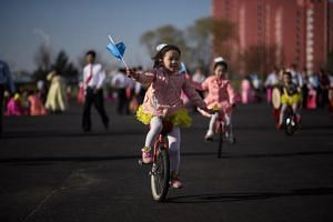Children riding unicycles during the opening of the 'April Spring Friendship Art Festival' outside a theatre in Pyongyang. The national rate of stunting amongst children has dropped to 19 per cent in 2017.