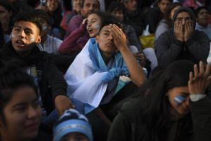Argentina fans react to the World Cup Russia 2018 match between Argentina and Croatia on a large screen at San Martin square in Buenos Aires, on June 21, 2018.