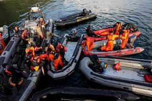 Members of an Indonesian search and rescue team prepare their diving gear as they search for victims of sunken ferry KM Sinar Bangun near Tigaras port in Simalungun, Indonesia, on June 21, 2018.